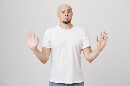 Portrait of stunned anxious bald caucasian bearded man raising hands in surrender gesture, looking with popped eyes and standing against gray background. Guy is afraid of furious girlfriend Stock Photo