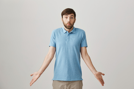 Studio portrait of attractive funny european guy, shrugging and making puzzled face while standing with spreaded hands over gray background. Man is confused as he do not know what is happening Reklamní fotografie
