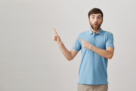 I have never seen anything similar. Portrait of attractive ordinary european male with beard and moustache pointing at upper left corner, being surprised and shocked, standing over gray background.