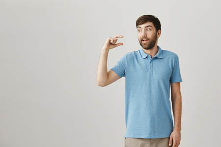 Small things may be more precious. Portrait of cute funny bearded guy with excited and positive expression shaping tiny or small thing over copy space with hand, talking about size and being pleased