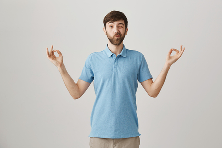 Funny attractive caucasian man with beard and moustache peeking and making faces while standing in meditating pose with zen gesture as if he is doing yoga over gray background