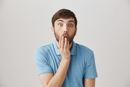 Stunned or impressed european man covering mouth with hand, bending towards camera with lifted eyebrows and popped eyes, standing against gray background. Guy accidentally heard shocking rumor 写真素材