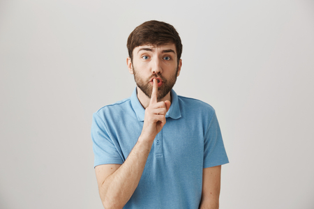 Worried european guy with beard in blue polo shirt making shush gesture while frowning and being concerned, standing against gray background. I will be in trouble unless you keep voice down