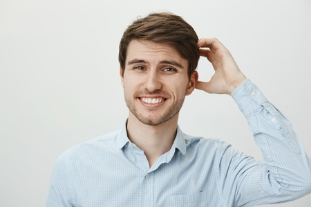 Studio portrait of hesitating puzzled attractive european guy with beard scratching head and smiling with nervous smile, wanting to say no, but being polite while standing over gray wall