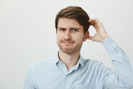 Puzzled ordinary european guy with bristle scratching head while looking with frustration at camera, being questioned or forgetting important information. Man cannot remember where he put keys