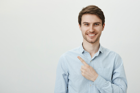 Portrait of handsome mature caucasian male entrepreneur pointing left with index finger while looking with confident bright smile at camera, being assured in his company successful deals Stock Photo