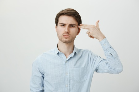 I am so miserable and bored. Portrait of attractive caucasian office worker mimicking handgun, showing weapons with gesture, holding ir near temple as if committing suicide, standing over gray wall