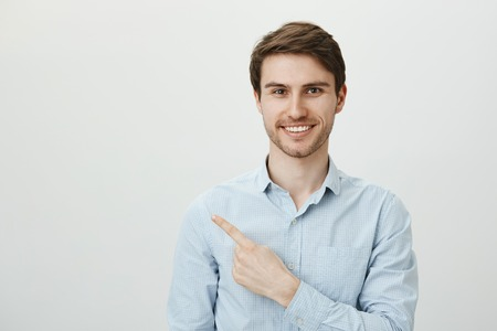 You will not regret about this copy space. Confident handsome adult unshaven male in blue-collar shirt pointing left with forefinger and smiling broadly, expressing professionalism over gray wall