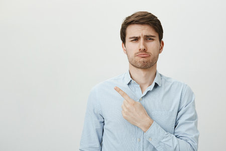 Such shame I missed all fun. Portrait of handsome sad caucasian guy pointing left with index finger whining and looking gloomy, being upset with issue or jealous, standing over gray background Stock Photo