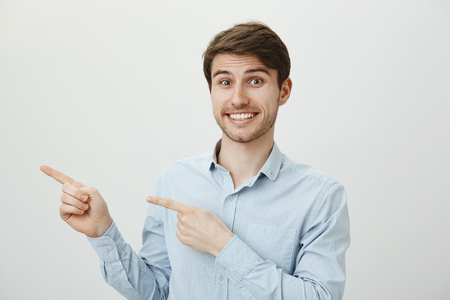 Let us go there together. Indoor shot of happy friendly handsome european businessman pointing left with index fingers and smiling broadly, asking out coworker to lunch together over gray background