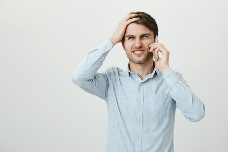 Oh no, it slipped my mind. Studio shot of attractive young entrepreneur in casual shirt punching forehead with palm and talking on smartphone, grimacing as recalling about important thing he forgot