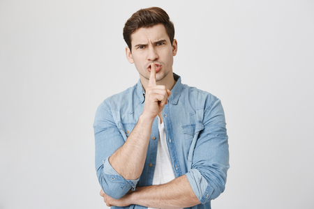 Portrait of serious handsome man, looking worried, showing shh gesture with index finger near mouth, isolated over white background. Cheater tells mistress to be quiet about their affair. 免版税图像
