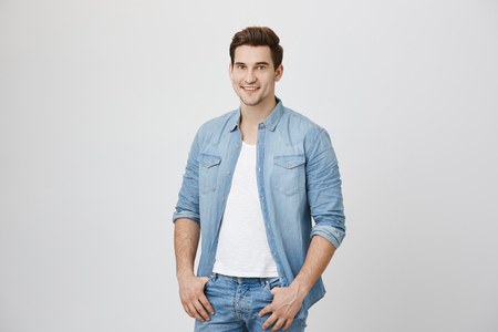 Handsome unshaven adult with happy and self-assured expression, looking at camera while holding hands in pockets, isolated over white background. Man did new haircut and thinks it really looks good