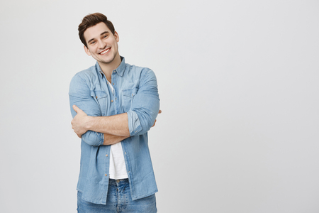 Handsome young male model with sincere happy smile and crossed hands looking at camera over white background, isolated. Man just signed deal that will bring him great profit