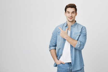 Good-looking guy with dark hair in denim shirt having surprised or shocked facial expression, pointing index fingers sideways at blank studio wall with copy space for promotional content