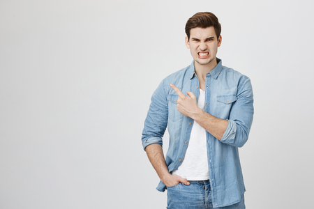 Indoor portrait of handsome young guy with aggressive expression, showing teeth while pointing at left upper corner with index finger, standing over gray background. Student pissed off