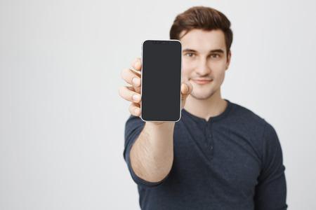 Ritratto di giovane modello europeo che annuncia nuovo smartphone, mostrandolo alla macchina fotografica, controllante fondo grigio. Il commesso mostra il nuovo dispositivo arrivato al negozio, spiegando le strutture