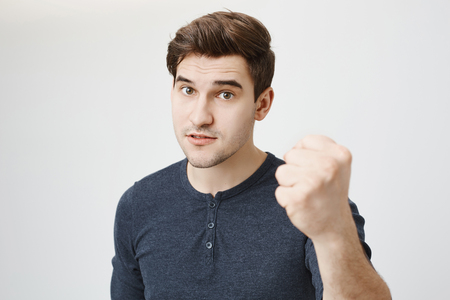 Studio shot of handsome european male model showing fist to camera and lifting eyebrows, demanding something over gray background. I swear next time you will be beaten if you do not behave properly