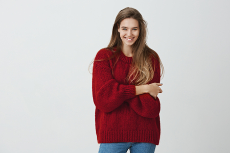 Show me what you have got. Studio shot of positive beautiful caucasian girl in trendy outfit standing with crossed hands and smiling from positive emotions over gray background