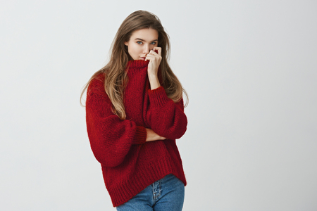 Girl hugged boyfriend and smells his perfume on her sweater. Portrait of sensual good-looking european model in trendy outfit pulling collar on face while standing against gray background.