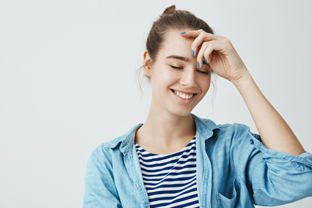 Positive emotions concept. Attractive woman with bun hairstyle holding hand on forehead while smiling with closed eyes, standing over gray background. Young artist creating new painting in mind Banque d'images
