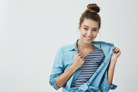 I can borrow you my shirt. Indoor portrait of cool attractive european female with bun hairstyle, taking off denim clothes while smiling with intrigued and flirting smile over gray background.