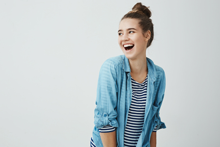 Hilarioous friends brighten life. Studio shot of positive emotive cute girlfriend with bun hairstyle bending right while turning aside and lauighing, being in good mood, hanging out with boyfriend Stock Photo
