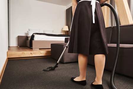 Cropped rearview of female housemaid cleaning floor of living room with vacuum cleaner, being busy and in hurry to finish before owner will come home, trying to remove all dirt and make apartment neat