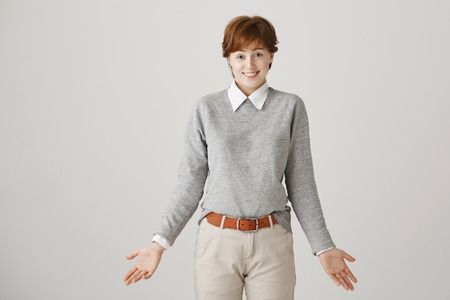 Woman did not have answer on question. Studio shot of attractive short-haired redhead female student shrugging with spread palms, smiling awkwardly and looking at camera over gray background