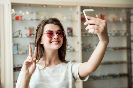 Good-looking feminine european woman in optician store taking selfie while trying on stylish sunglasses showing peace or victory sign and smiling at camera, being satisfied with purchase Stockfoto