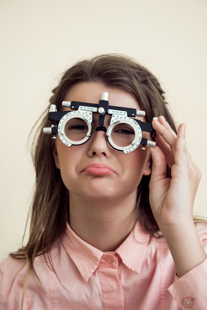 Sad girl has eye problems. Portrait of upset gloomy european woman in ophthalmologist office, testing vision while sitting and wearing phoropter, regretting that she spoilt sight near computer