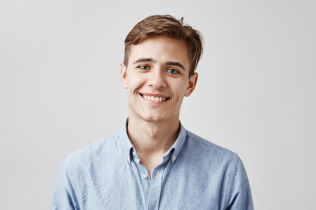Cute boy with brown hair and beautiful smile standing next to the wall. His birthday is today so coworkers made surprise party. Guy looks happy he did not expected they will remember.