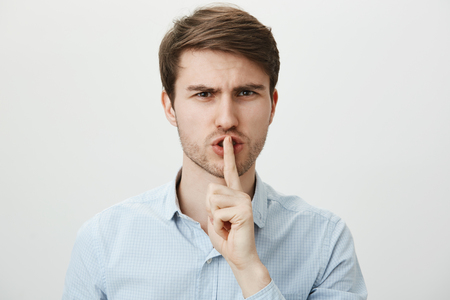 Do not cause noise, shh. Portrait of strict serious handsome guy in casual blue shirt holding index finger over mouth, saying shush and frowning with displeased expression, standing over gray wall