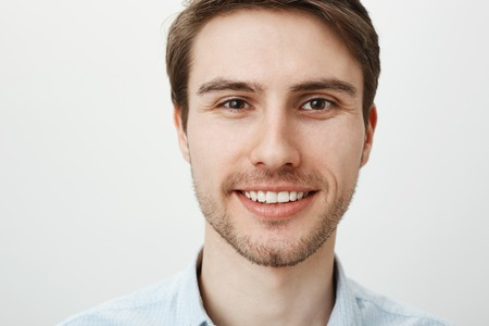 Close-up portrait of attractive confident adult male with bristle smiling broadly while looking at camera, standing against gray background. Calm and friendly office worker explains chores to newbie Stock Photo