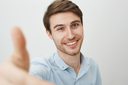 Here, let me lend you hand. Portrait of charming friendly caucasian man pulling hand towards camera as if trying to grab it or help girlfriend get down, smiling broadly over gray background