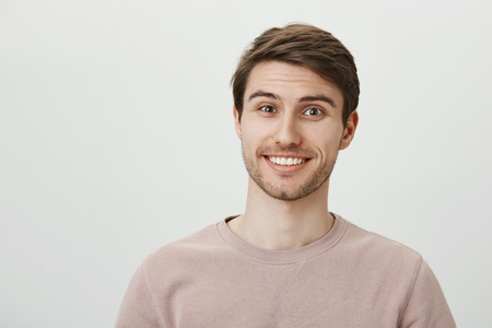 Your life is unbelievable. Interested handsome european male student with bristle smiling cheerfully while posing against gray background. Man listents amazing story of friend who travelled overseas