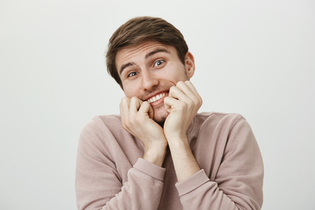 Portrait of pleased good-looking funny man holding clenched fists in mouth, smiling and tilting head aside, being charmed by something adorable and amazing over gray background. Guy likes cute things