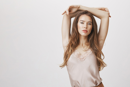 Express your inner beauty. Indoor shot of sensual sexy woman in trendy outfit posing with hands above head, looking flirty and seductively at camera, being in romantic mood, relaxed over gray wall Stock Photo