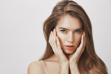 美しさの自然な磁気の外観。透明な肌と魅力的な顔の特徴を持つ素晴らしいヨーロッパの女性は、優しく顔に触れ、カメラで官能的に見つめ、美し