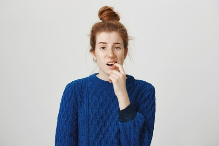 Worried and submissive redhead girl with cute freckles and bun hairstyle biting finger and frowning looking frustrated and uncertain, wanting to ask question but being shy, standing over gray wall