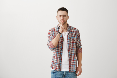Remain silent and nobody will get hurt. Indoor portrait of serious confident male with attractive appearance, standing over gray background, showing shh gesture with index finger on mouth Stock Photo
