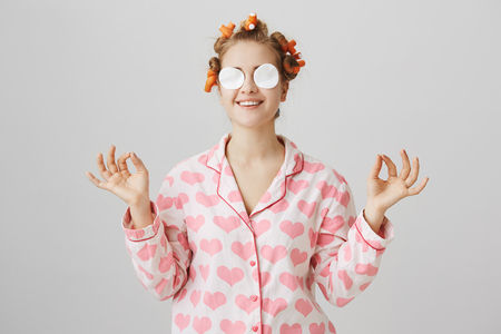 Keep calm and make yourself beautiful. Cute glamorous woman in hair curlers, pyjamas and cotton pads on eyes, holding hands in zen gesture as if meditating and relaxing while doing cosmetic procedures Stock Photo