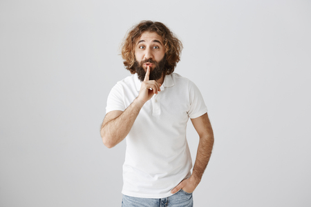 Keep your voice down please. Portrait of attractive friendly eastern male with beard saying shh while showing shush gesture with index finger over lips, being worried about secret he told friend Stock Photo