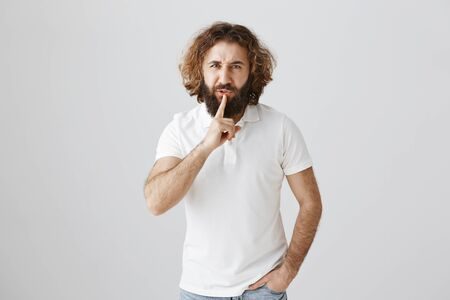 Studio shot of bothered and angry eastern man with curly hair and long beard showing shh or shush gesture with index finger over mouth, frowning, wanting some silence over gray background