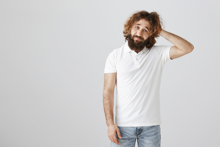 Man expressing his unawareness and confusion. Portrait of attractive adult eastern guy with curly hair and beard scratching head with gloomy expression, being bothered with uncertainty or doubt