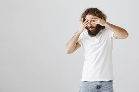 Intrigued and interested mature eastern man with curly hair and beard covering eyes with palms and peeking through fingers, being curious what is happening, standing over gray background Stock Photo