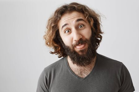Troubles fear of laugh. Indoor shot of carefree attractive easter guy with curly hair and beard showing tongue and making funny face while standing over gray background, fooling around