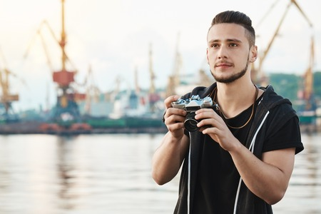 When hobby becomes beloved work. Portrait of dreamy creative young guy with beard holding camera and looking aside with thoughtful pleased expression, taking photos of harbour and sea while walking Reklamní fotografie