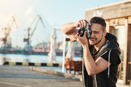 Attractive young male photographer walking along harbour, making photos of cool yachts and people, looking through camera focused on great shot, having flair for photojournalism 스톡 콘텐츠