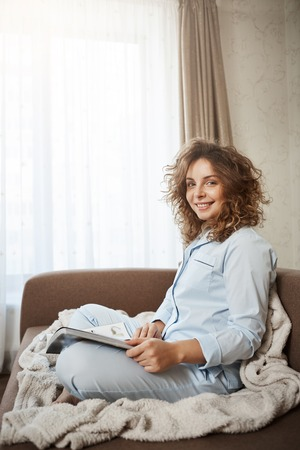 Indoor vertical shot of cute cozy wife with curly hair in nightwear sitting on sofa with blanket, reading magazine, enjoying perfect morning, having day-off, relaxing, gazing at camera with kind smile